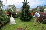 Bride and groom play swingball at wedding reception